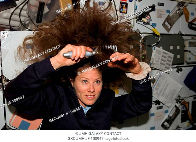 Astronaut Tracy Caldwell, on the mid deck of the Space Shuttle Endeavour, brushes her hair as she prepares to participate in the shuttle crew's supply transfer...