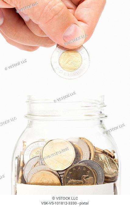 Man putting coin into jar