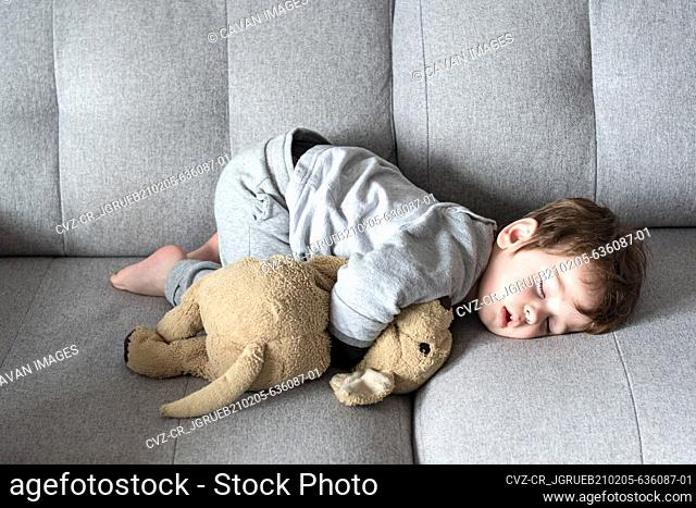 Small child sleeping on the sofa in a strange posture