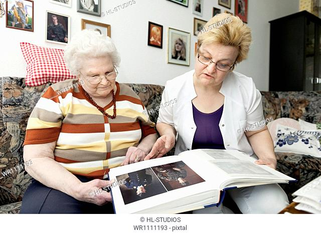 Geriatricnurse and old woman looking into photo album