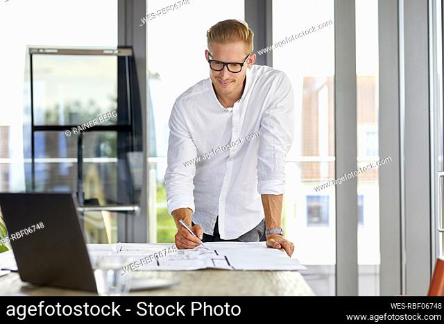 Smiling young man working on blueprint on desk in office