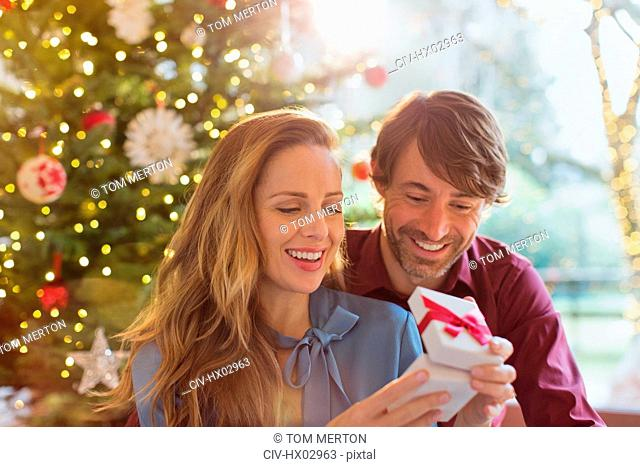 Husband watching wife opening Christmas gift in front of Christmas tree