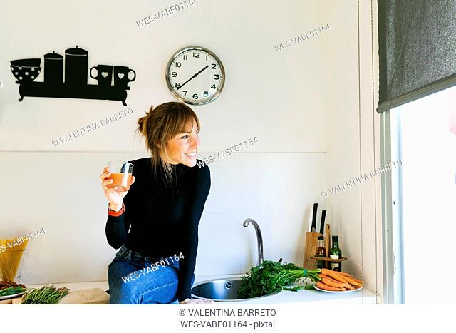 Young woman drinking fresh grapefruit juice in her kitchen