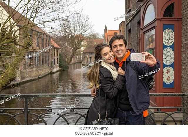 Couple taking smartphone selfie, Bruges, Flanders, Belgium