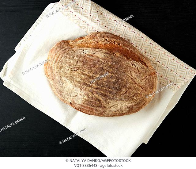 baked oval rye bread on a wooden black board, top view