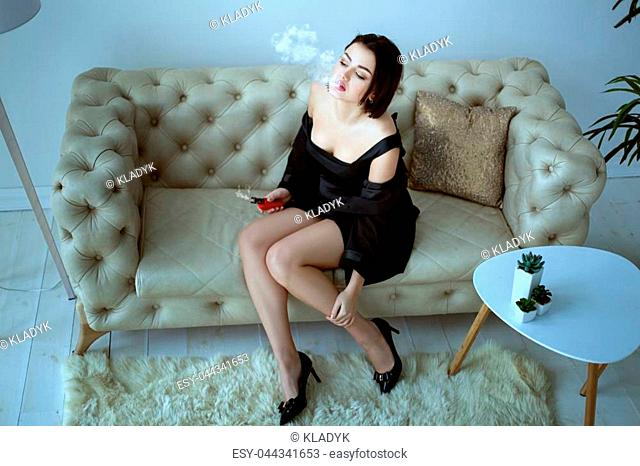 Beautiful woman smokes an e-cigarette while sitting on the couch