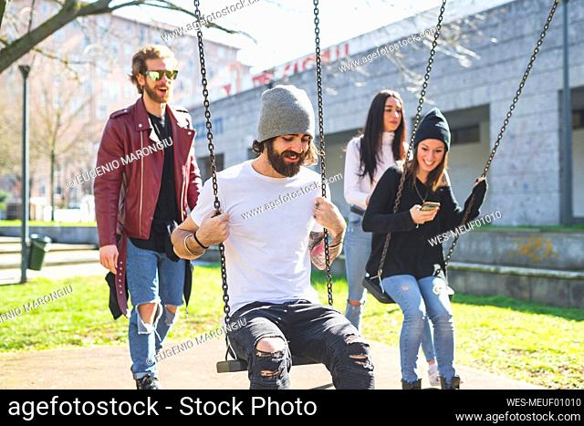 Man and woman pushing friends sitting on swings in park during sunny day