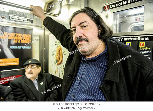 Subway, New York, Manhattan. Caucasian man wearing a mustage and his retired father, commuting by subway through Manhattan