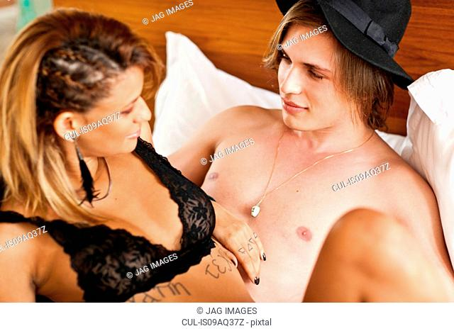Undressed young couple reclining on hotel bed