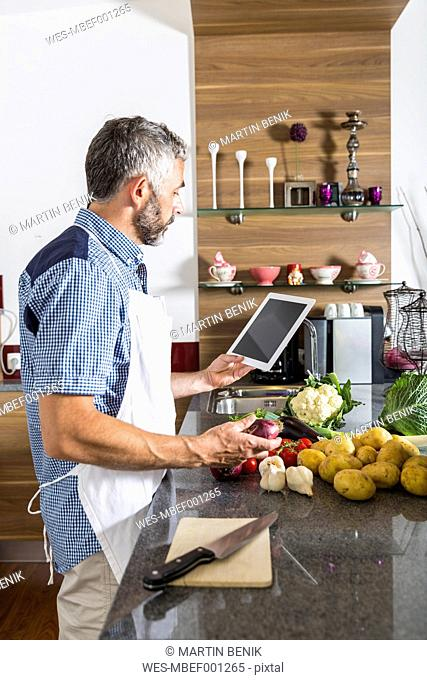 Austria, Man in kitchen with digital tablet preparing food