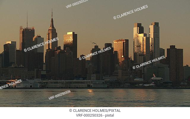 The mid-town Manhattan skyline is lit by sunlight just after sunrise in New York City