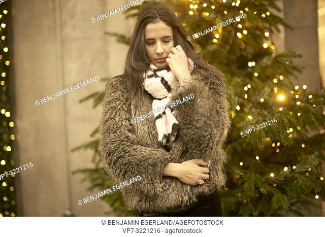 portrait of pensive young woman with closed eyes in front of Christmas tree lights, wearing fashionable winter clothes, in city Munich, Germany