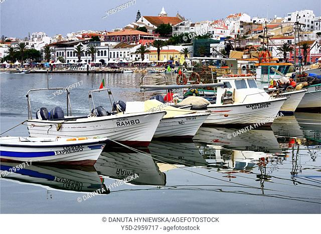Traditional fishing boats moored in the harbour, in background old town with historic food market, Ciencia Viva - cultural center and Sao Sebastiao church
