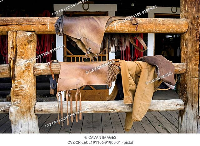 Leather chaps hang on a wood porch railing after horseback riding