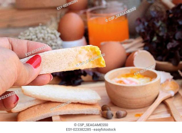 soft-boiled egg with bread on wood background