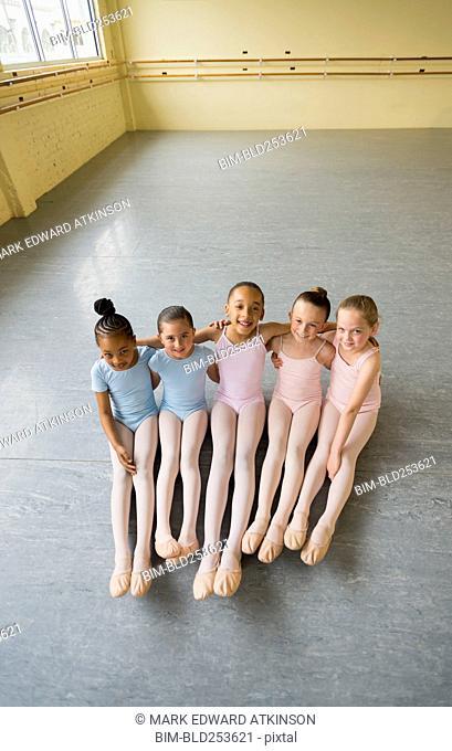 Portrait of smiling girls hugging on floor of ballet studio