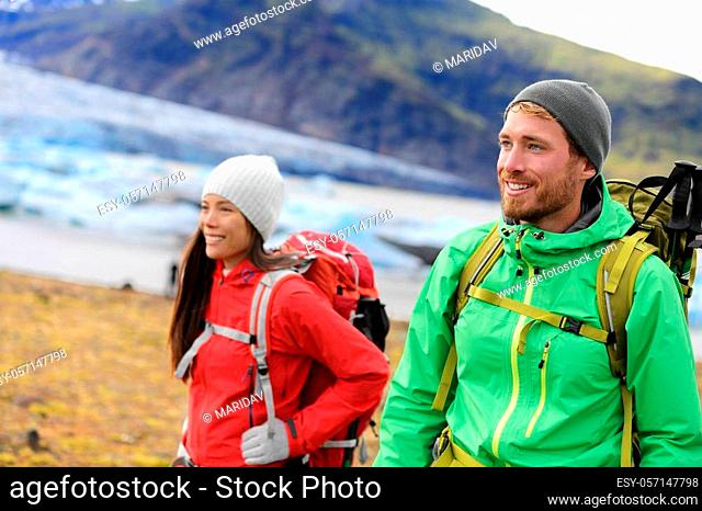Hiking adventure travel people living active healthy lifestyle wearing jackets and backpacks on Iceland by glacier and glacial lagoon / lake of Fjallsarlon