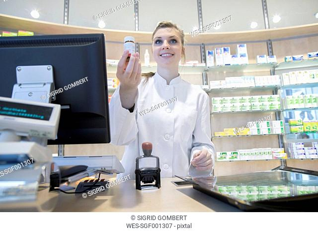 Young pharmacist in pharmacy, smiling