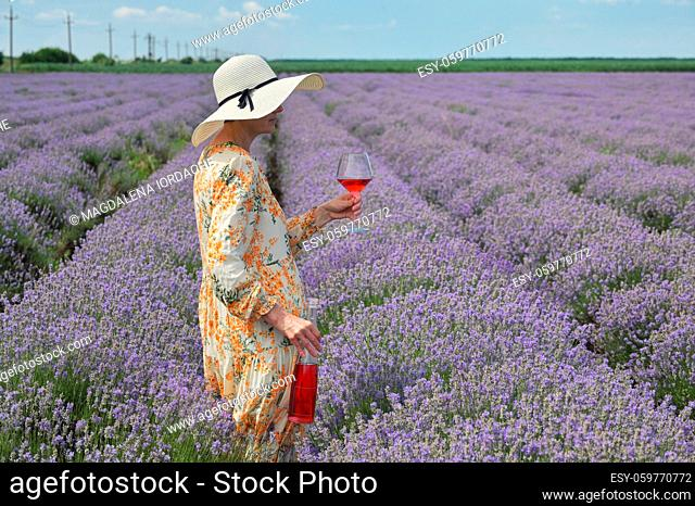 Woman with Rose Wine In Lavender Summer Field