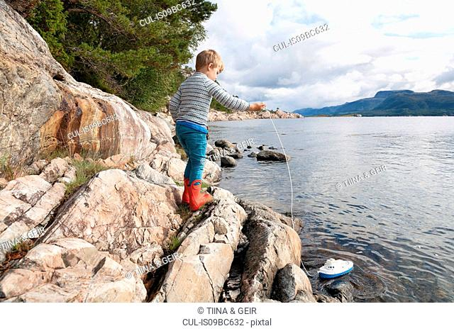 Boy standing on rock by fjord playing with toy boat, Aure, More og Romsdal, Norway