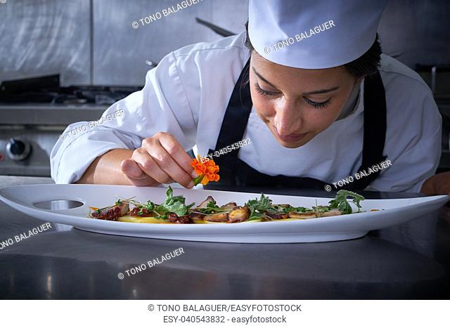 Chef woman garnishing flower in dish at stainless steel kitchen
