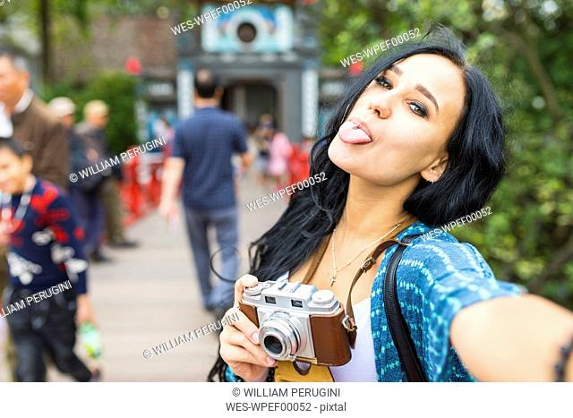Vietnam, Hanoi, young woman with an old-fashioned camera sticking her tongue out