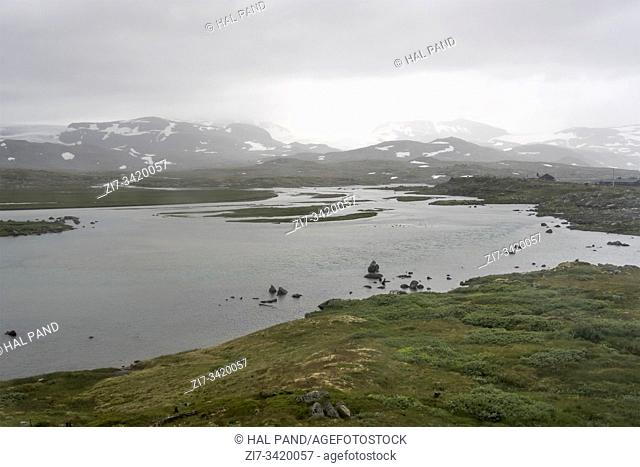 landscape with low clouds on lake in high valley of barren mountains with some summer snow, shot under bright cloudy summer light near Finse, Norway