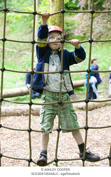 A young boy on a ropes course at Brathay in the Lake District UK