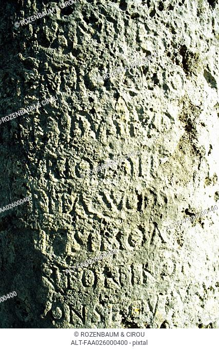 Text carved in stone, close-up, full frame