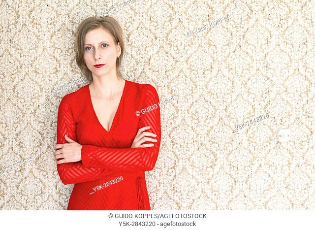 Tilburg, Nethetlands. Classical Music Teacher wearing a Red Dress leaning against her vintage reading room wall