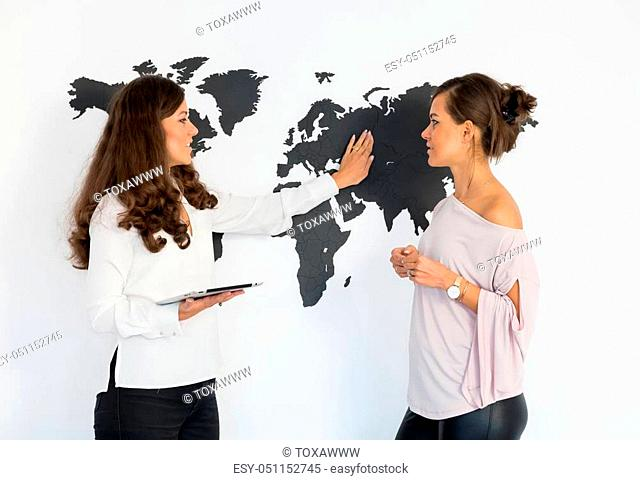 Two young women twins discuss business on the background of the world map