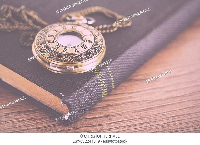 Pocket watch and book against a rustic wooden background Vintage Retro Filter