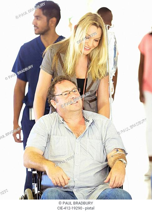 Woman wheeling father in hospital hallway