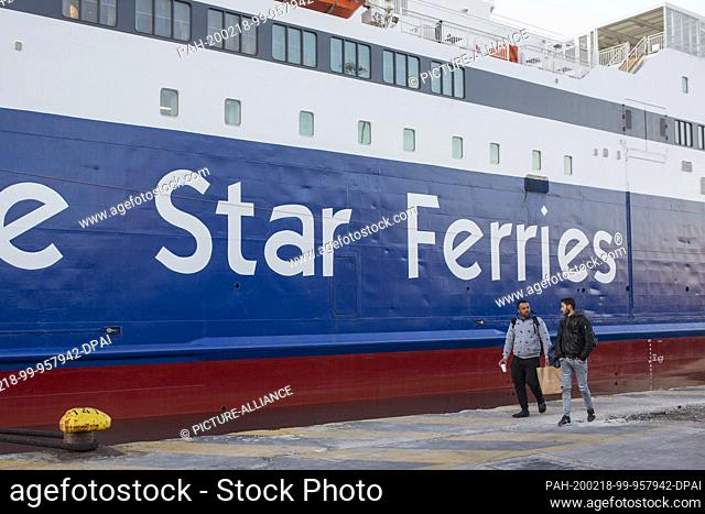 18 February 2020, Greece, Piräus: Two men walk along a docked ferry in the port of Piraeus during a 24-hour strike. Extensive strikes today have led to...