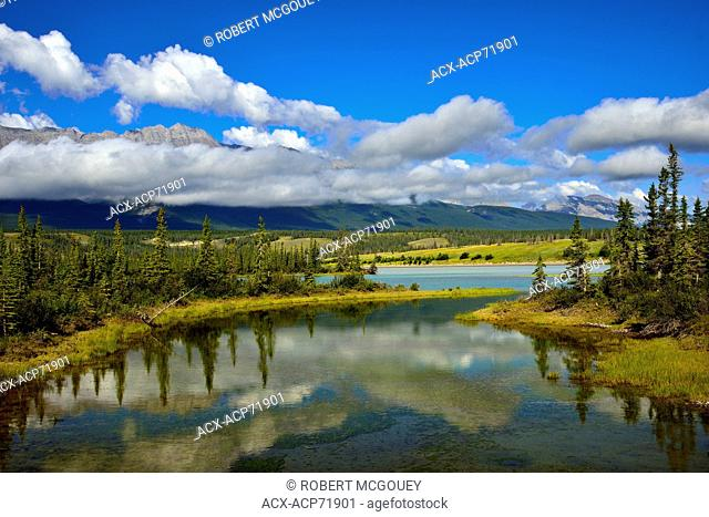 A summer landscape of Jasper Lake and the low hanging clouds over a mountain range in Jasper National Park in Alberta Canada
