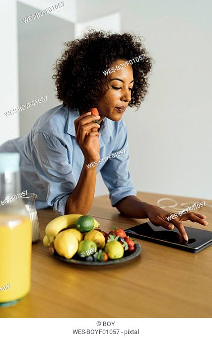 Woman using digital tablet and having a healthy breakfast in her kitchen