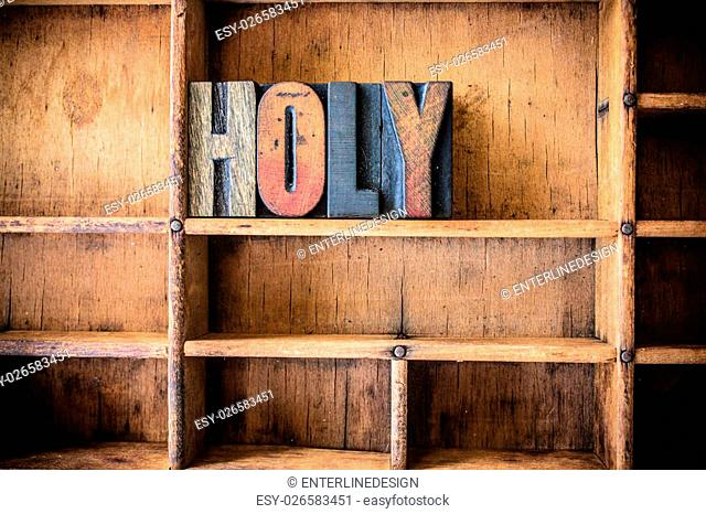 The word HOLY written in vintage wooden letterpress type in a wooden type drawer