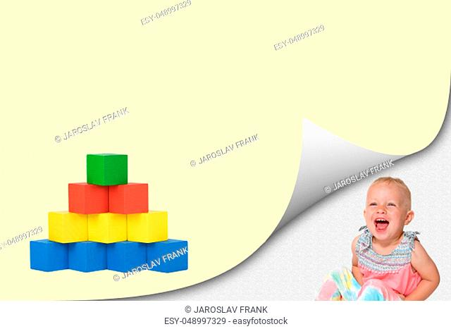 Blank page with curl effect and laughing toddler girl sitting in an exposed corner. Laughing girl is looking at pyramid of colorful wooden toy cubes