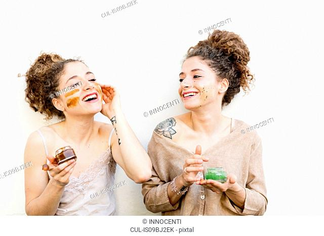 Fashion blogger twins applying face masks, white background