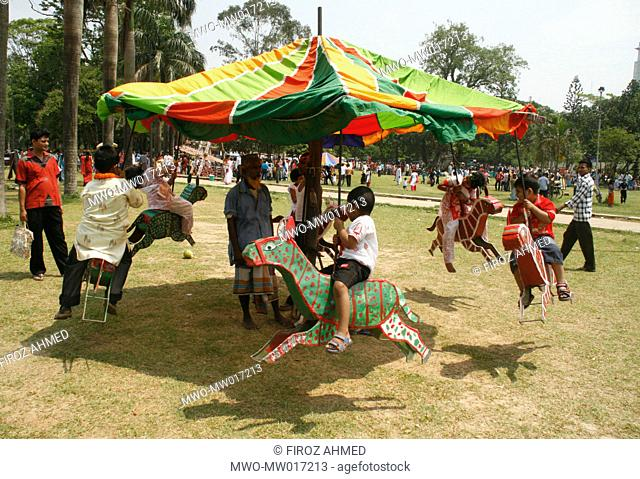 A group of children riding merry-go-round, at a play ground, in front of Dhaka University, on the occasion of the Bangla New Year festivities Bangladesh Monday...