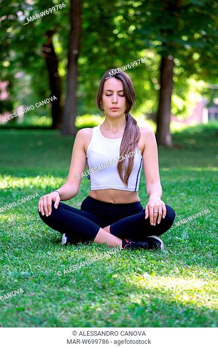 Ragazza che fà yoga in un parco pubblico
