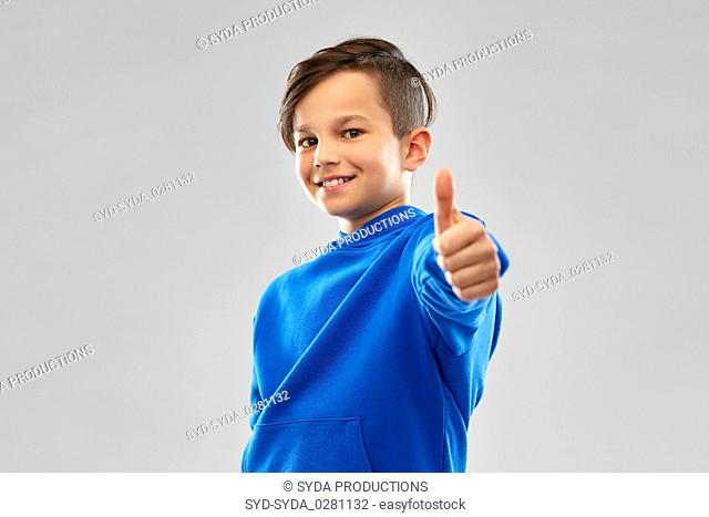 smiling boy in blue hoodie showing thumbs up