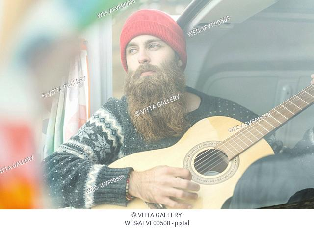 Portrait of hipster in van playing guitar