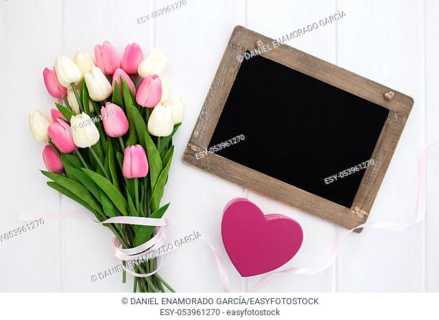 Blackboard on a wooden white background with tulips bouquet