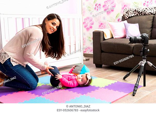 Gorgeous young Hispanic mother recording a video for her parenting blog with her baby