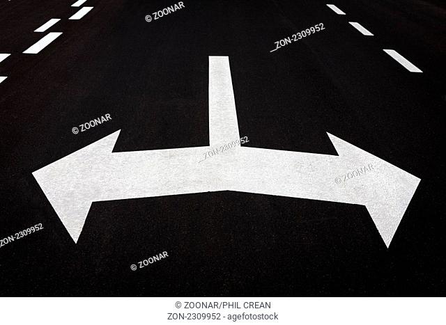 Left and right turn arrows painted on tarmac roadway. Concept for turning, decision, choice, which way, right, left