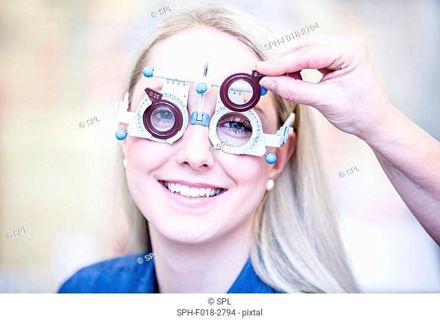 Portrait of cheerful young woman having eye examination in optometrist's shop, close-up