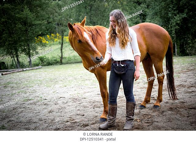 A teenage girl to feed and care for her horse; British Columbia, Canada