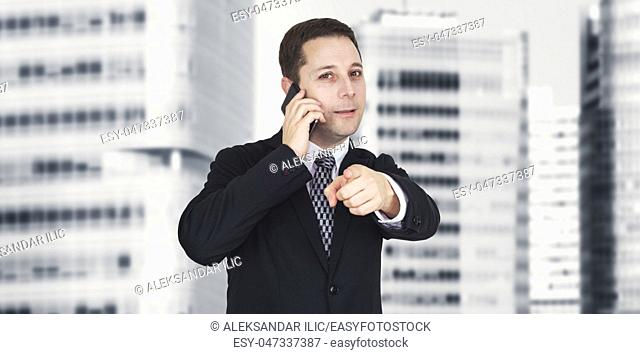 Businessman Talking On The Phone And Pointing Index Finger Towards Camera With Business City and Corporate Buildings In Background