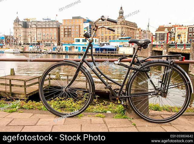 Amsterdam, Netherlands. Colourful bike over a bridge and city channels